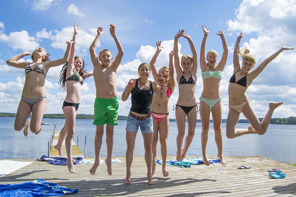 Hoppande deltagare vid sjön