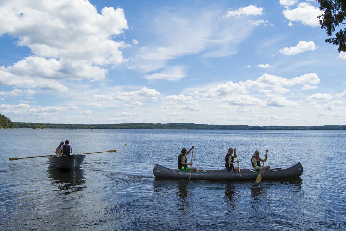 Deltagare och ledare åker kanot på sjön.